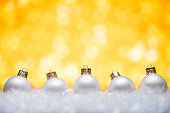 New Year and Christmas background. White Christmas toys lie in the snow, with a bright background
