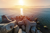 Beautiful sunset seascape. Breakwaters tetrapods ashore of pier. Cargo ships on the horizon. Travel dreams and motivation
