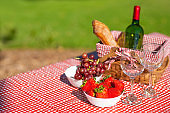picnic basket checkered with a tablecloth wine, baguette, strawberry, glasses, banner