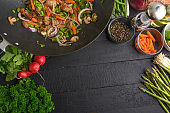 Asian cuisine, Flat lay, cooking and frying meat with vegetables. On a black wooden background with space, culinary background.