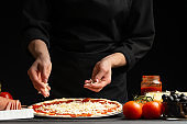 Chef cooks pizza, sprinkled with mozzarella cheese