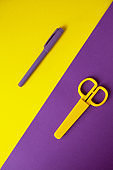 Yellow kid's stationery scissors on purple background, purple pen on yellow background. Yellow and purple background halve image diagonally. Back to school concept. Top view of office supplies.
