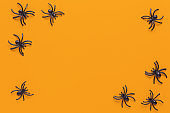 Halloween holiday flat lay. Black spiders on orange background with copy space. Minimal style. Horizontal. Trick-or-treat concept