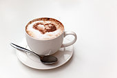 Cappuccino cup on white table background. Foam is decorated with cinnamon heart. Copy space. Top view, located at side of frame. Horizontal. Mock up for social media, food blog, lifestyle