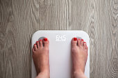 Woman stands on white modern electronic scales, which show 64.5 kg. Only feet are visible. Scales stand on gray wooden floor. Space for text. Healthy lifestyle, diet, weight loss concept. Horizontal.