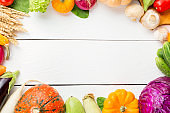 Assorted raw organic fresh vegetables on white wooden table. Fresh garden vegetarian food. Autumn seasonal image of farmer table with mushrooms, rye, cucumbers, tomatoes and eggplant. Free space.