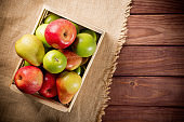 Ripe green and red apples with pears in a wooden box on sackcloth and brown wooden rustic background. Autumn seasonal image with top view.