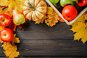 Ripe apples in a box with pumpkins, apples and pears near autumn leaves on dark wooden background. Autumn seasonal image. Top view with free space.