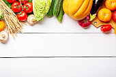 Assorted raw organic fresh vegetables on white wooden table. Fresh garden vegetarian food. Autumn seasonal image of farmer table with mushrooms, rye, cucumbers, tomatoes, eggplant, melon and onion.