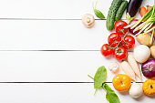 Vegetarian eating. Healthy organic vegetables composition on white wooden table with copy space. Top view.