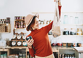 Minimalist vegan style young woman with cotton reusable net mesh bag and reusable glass coffee cup on background of goods of zero waste shop.