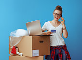 woman speaking on a cell phone near cardboard box with credit card and laptop