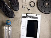Closeup on workout log in clipboard and tablet PC