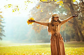 smiling woman with yellow leaves with raised arms rejoicing