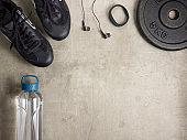 sneakers, headphones, fit tracker, bottle of water, weight plate
