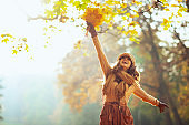 happy woman with yellow leaves rejoicing outside in autumn park