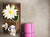 tray with fragrant stuff for aroma yoga, beads and pink yoga mat