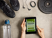 sneakers and female hands holding tablet PC with workout app