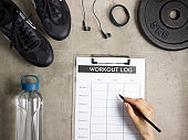 Closeup on female hand filling workout log in clipboard