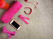 pink dumbbells, towel, bottle of water, fit tracker, smartphone