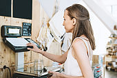 Woman chooses and buys products in zero waste shop