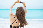 middle age woman on white beach taking photo with mobile phone