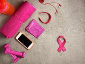 dumbbells, towel, smartphone and pink ribbon shaped elastic band