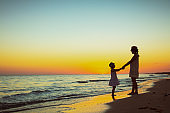 mother and daughter on ocean shore at sunset having fun time