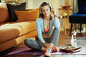relaxed healthy sports woman listening to music with headphones