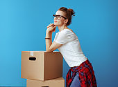 pensive modern woman near cardboard boxes on blue