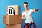woman showing thumbs up near cardboard box with calculator