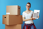 pensive modern woman near cardboard box with calculator on blue