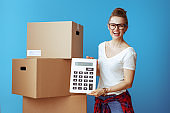 smiling woman near cardboard box showing calculator on blue