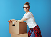 young woman in white t-shirt near cardboard boxes on blue