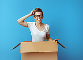 happy modern woman in white t-shirt in cardboard box on blue
