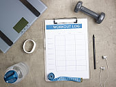 weight scales, black pen and workout log on clipboard