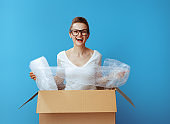 woman in a cardboard box with air bubble film packaging material