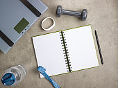 weight scales, fitness tracker, pen and opened notebook