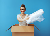 woman in a cardboard box giving air bubble film packaging material