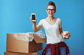 woman showing phone blank screen near cardboard box with piggybank