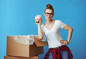 young woman near cardboard box showing piggybank on blue