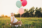 Baby girl in wicker basket with pink balloons in sunlight at summertime.