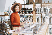 Young woman doing shopping with wicker bag and glass jars  in plastic free grocery store.