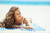relaxed young woman laying on striped towel on seashore