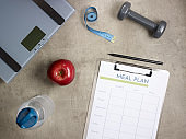 weight scales, apple, tape measure and clipboard with meal plan