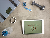 weight scales, tape measure and tablet with heart rate app