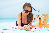 pensive middle age woman laying on round towel and sun tanning