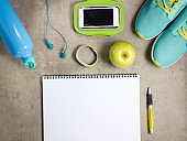 apple, headphones, fitness tracker, bottle of water and notebook
