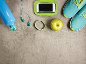 green apple, headphones, sneakers, fit tracker, bottle of water