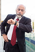 Serious focused businessman consulting watch near office